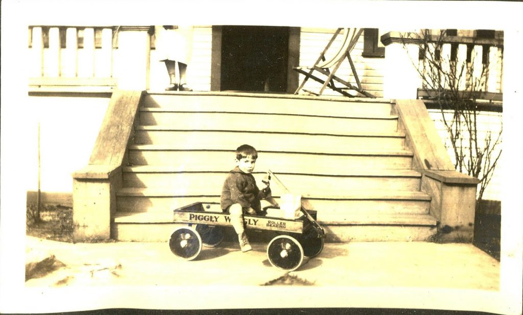 A young cousin in Vancouver, BC, Canada on his Piggly Wiggly wagon. 1920s.